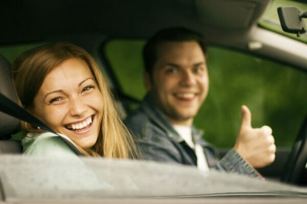 Two person smiling inside the car
