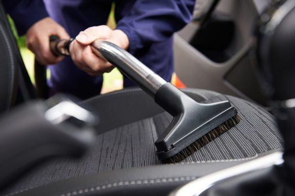 Man vacuuming the car seat
