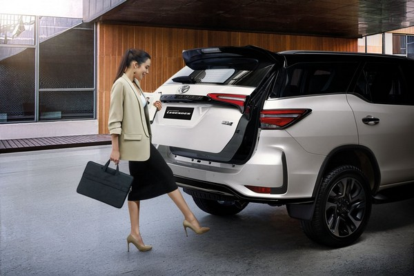 a woman besides a Toyota Fortuner